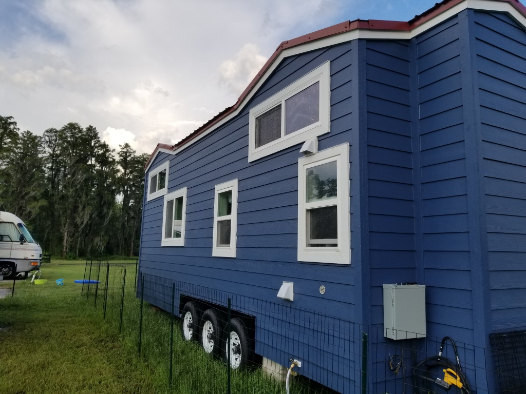 blue tiny house on wheels on farm. blue skies and green grass