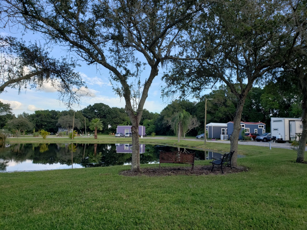 four tiny houses in a tiny house community around a pond