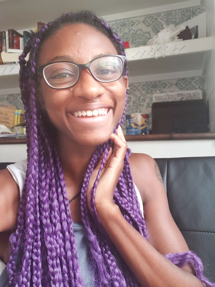 black girl with purple hair and glasses in front of bookshelf