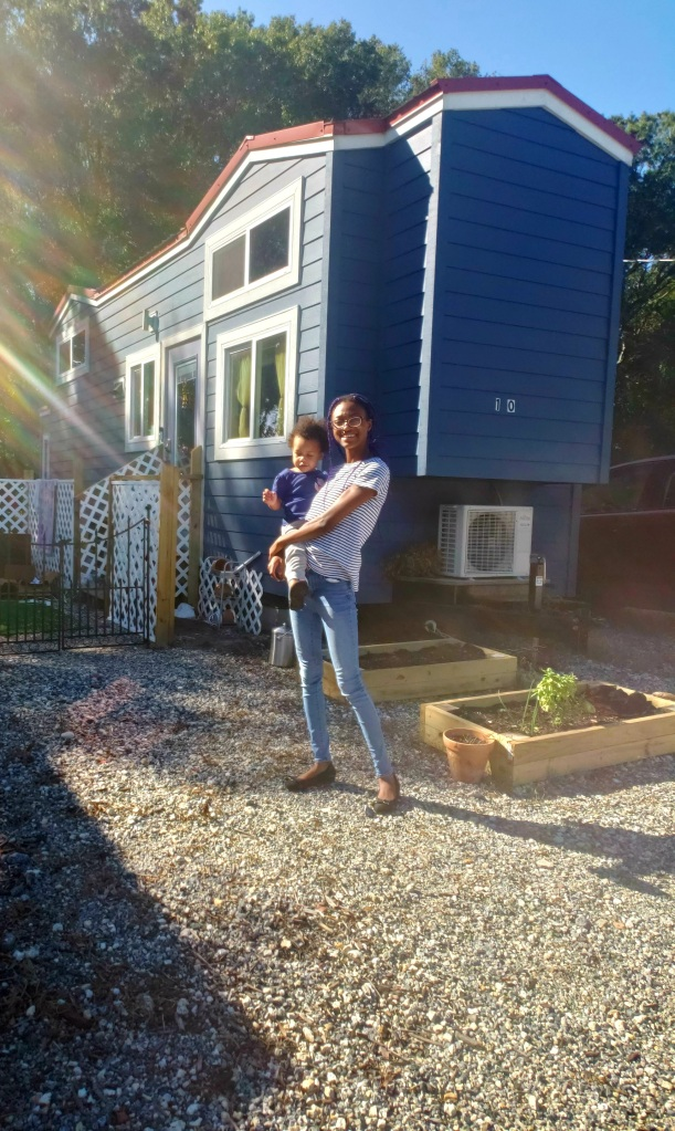 black woman holding baby standing in front of house
